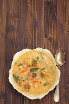 Zupa jarzynowa z fasolą, szpinakiem i makaronem w białej misce
