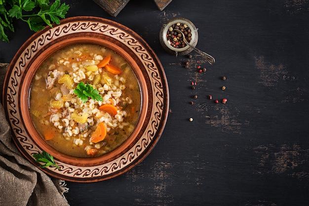 Zupa jęczmienna z marchewką, pomidorem, selerem i mięsem na ciemnym tle. widok z góry.