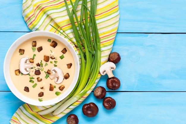 Zupa kasztanowa na niebieskim polu z żółtą serwetką i przyprawami.