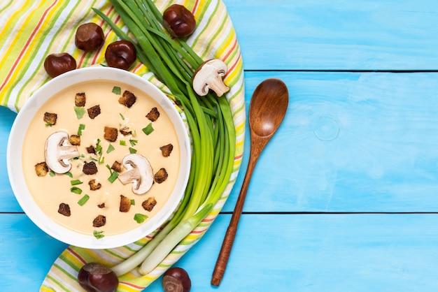 Zupa kasztanowa na niebieskim stole z żółtą serwetką i przyprawami. widok z góry. miejsce do skopiowania.