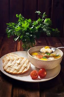 Zupa khash na talerzu, chleb i pęczek pietruszki