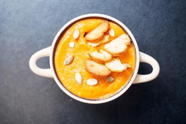 Zupa krem dyniowy z grzankami na czarnym stole z przyprawami. wysokiej jakości zdjęcie