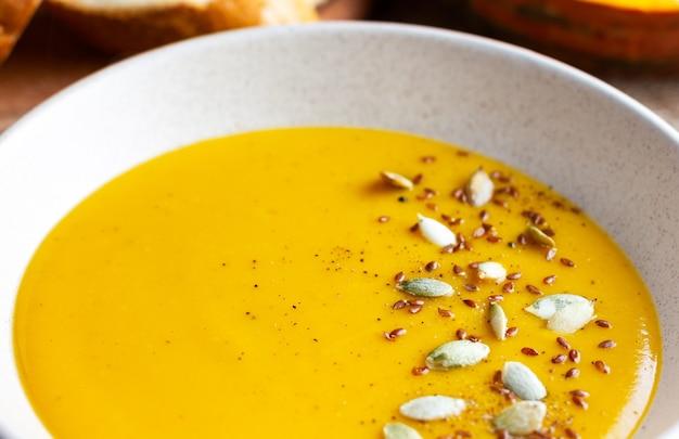 Zupa krem dyniowy z pestkami dyni zbliżenie jesienne śniadanie dietetyczne jedzenie