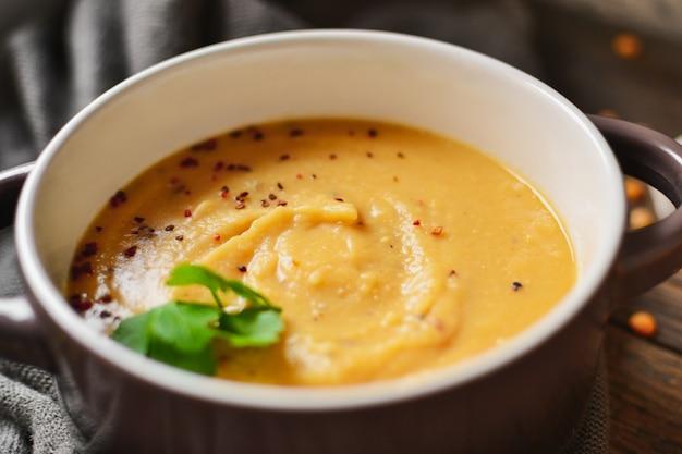 Zupa krem grochowa w misce na drewnianym stole. puree z grochu i owsianka. ścieśniać.