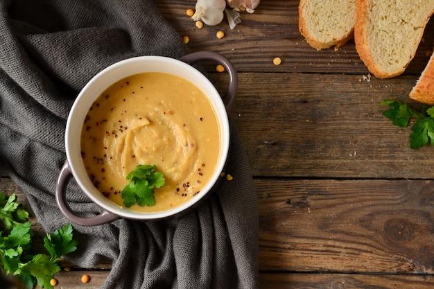 Zupa krem grochowa w misce na drewnianym stole. puree z grochu i owsianka. widok z góry