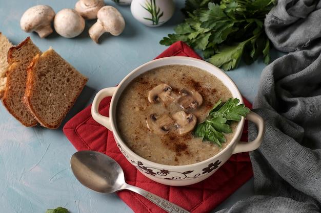 Zupa krem grzybowa z pieczarek i soczewicy w talerzu na jasnoniebieskim tle, zbliżenie
