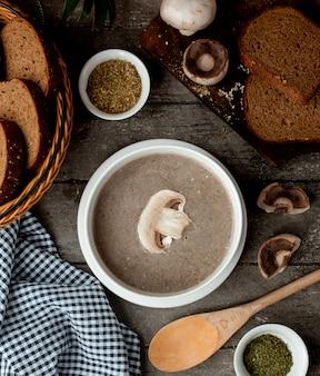 Zupa krem grzybowa ze śmietaną w białej misce i koszyku