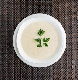 Zupa krem grzybowa ze śmietaną w białej misce