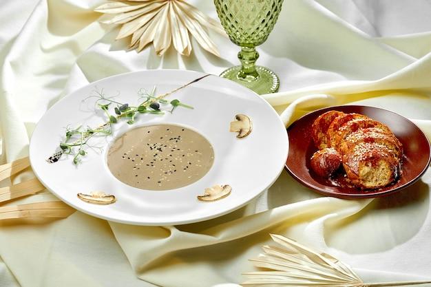 Zupa krem grzybowy z bułką w białym talerzu na obrusie