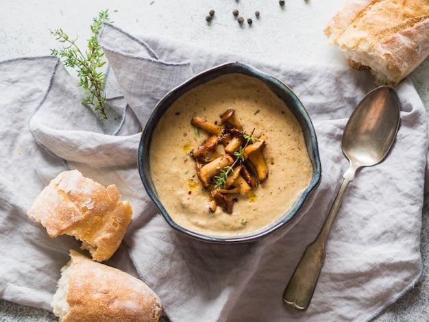 Zupa krem kurkowy w niebieskiej misce, bagietce i świeżym tymianku