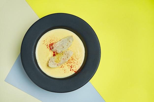 Zupa krem serowy w czarnej misce z krakersami, smażonym chlebem i przyprawami. smaczne jedzenie na lunch. kolorowa powierzchnia