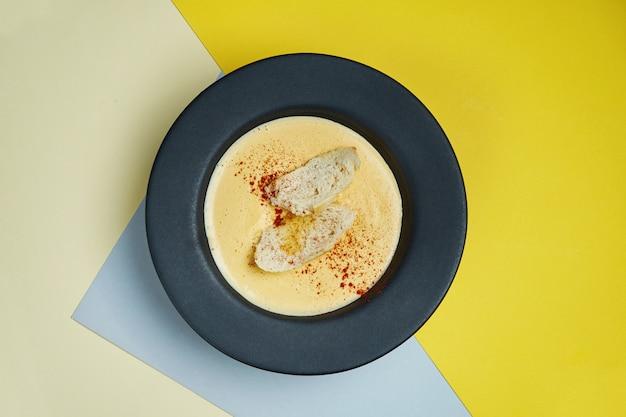 Zupa krem serowy w czarnej misce z krakersami, smażonym chlebem i przyprawami. smaczne jedzenie na lunch.