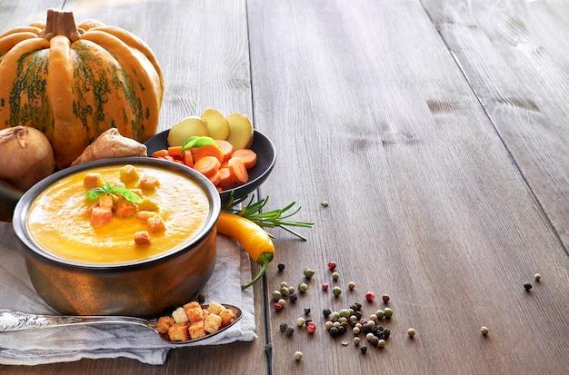 Zupa krem z dyni, marchewki i imbiru w ceramicznej patelni na drewnianym stole