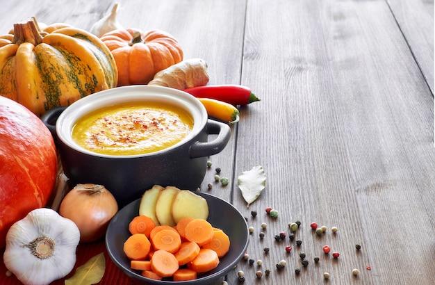 Zupa krem z dyni, marchwi i imbiru na ciemnym ceramicznym patelni na drewnie