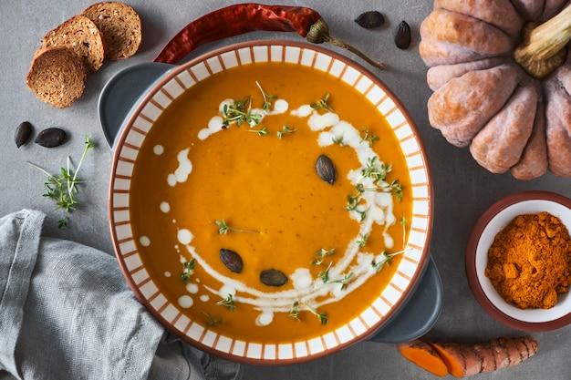 Zupa krem z dyni w ceramicznej misce doprawiona tymiankiem, śmietaną i grzankami, składniki dookoła