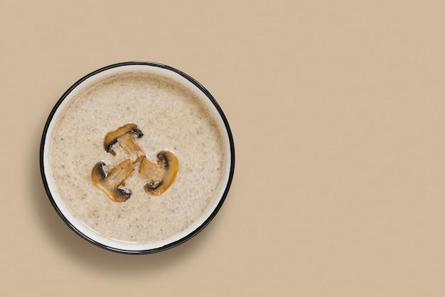 Zupa krem z pieczarek grzybowych na beżowym tle widok z góry