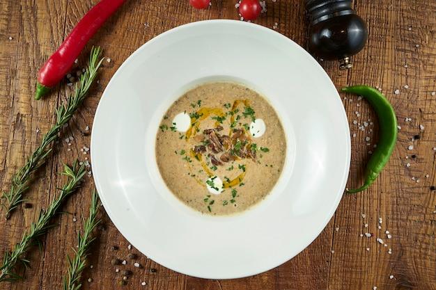 Zupa krem z pieczarek z pieczarkami, przyozdobiona smażonymi grzybami, oliwą z oliwek i tartym parmezanem w szarej misce na drewnianej powierzchni
