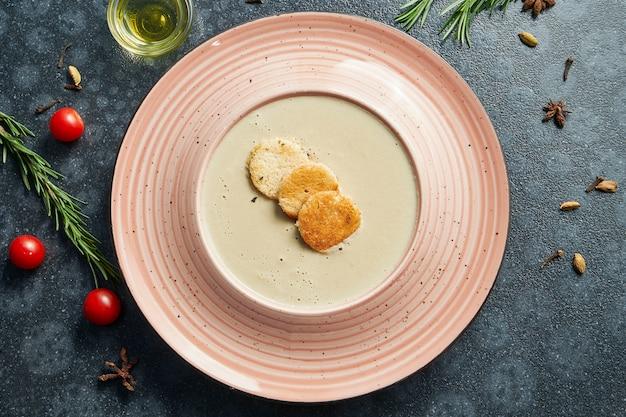 Zupa krem z pieczarek z pieczarkami, przyozdobiona szynkami w różowej misce na ciemnej powierzchni