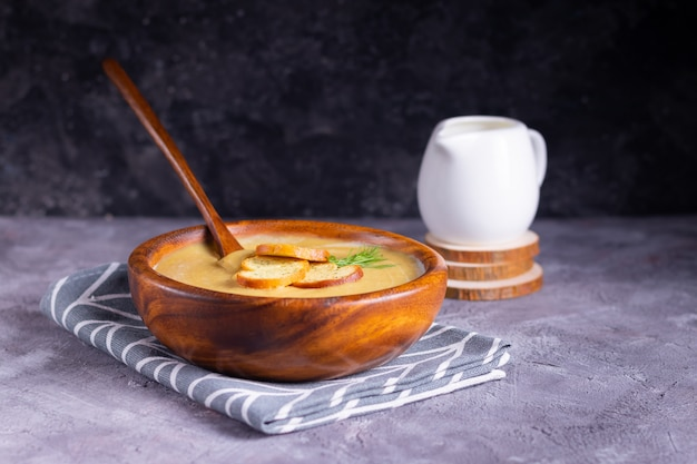 Zupa krem z soczewicy i dyni z koperkiem na drewnianym talerzu z drewnianą łyżką ze śmietanką na drewnianych podstawkach na szarej powierzchni