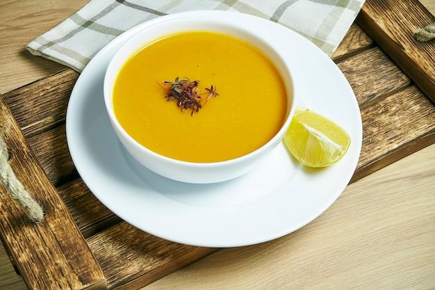 Zupa krem z soczewicy z plasterkiem cytryny na drewnianej tacy w białej misce. zdrowe i wegańskie jedzenie. zzielenieć. ścieśniać