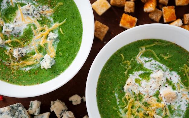 Zupa krem ze szpinaku i brokułów. z dodatkiem parmezanu i sera pleśniowego z grzankami. drewniana powierzchnia.