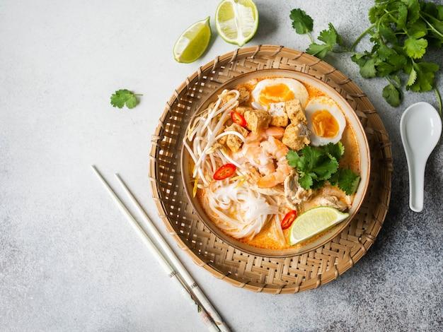 Zupa laksa z malezyjskim makaronem z kurczakiem, krewetkami i tofu w misce na szarej powierzchni