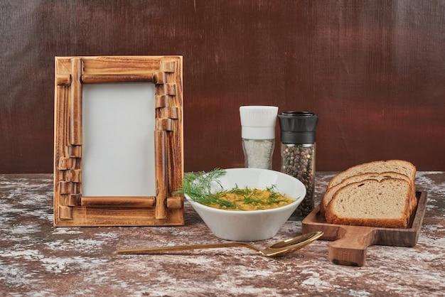 Zupa makaronowa z ziołami i kromkami chleba.