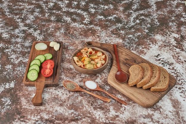 Zupa makaronowa z ziołami i sosem pomidorowym i sałatką warzywną dookoła.