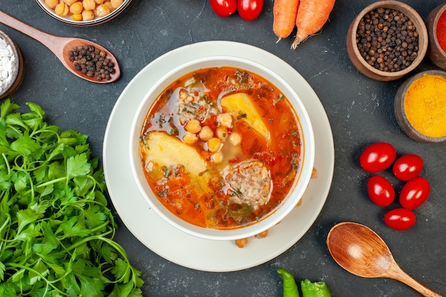 Zupa mięsna z widokiem z góry z zieleniną i przyprawami na ciemnym tle