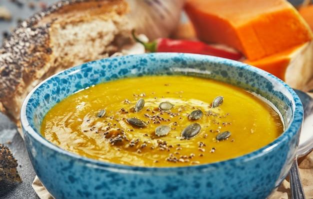 Zupa pomarańczowa w niebieskim talerzu z pestkami dyni i ziarnami chia
