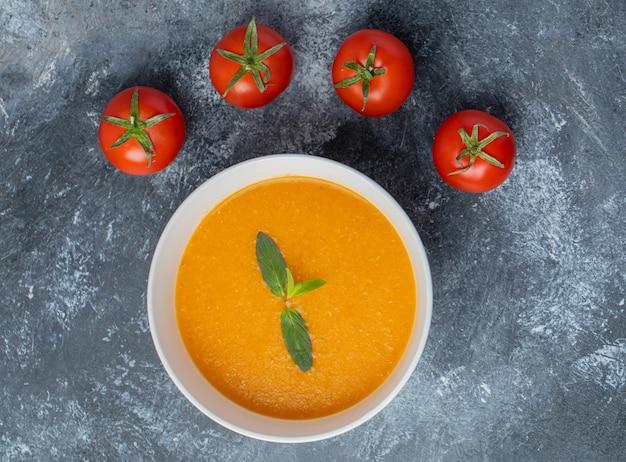 Zupa pomidorowa w białej ceramicznej misce ze świeżymi pomidorami na szarym stole.