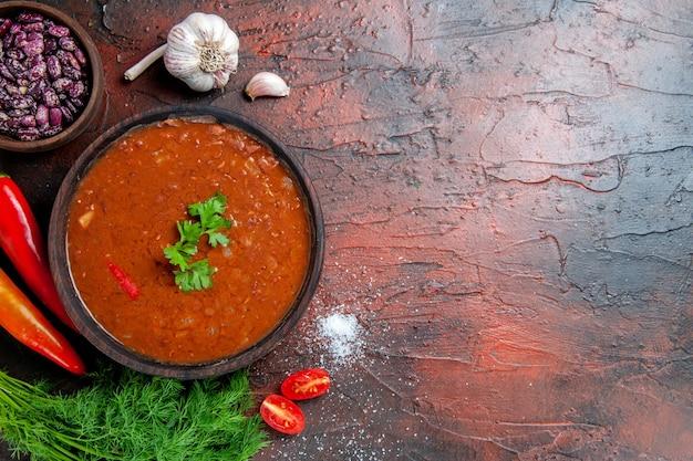 Zupa pomidorowa w brązowej misce i różne przyprawy czosnkowo-cytrynowe na mieszanym materiale kolorystycznym