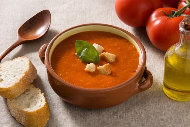 Zupa pomidorowa w brązowej misce przyozdobionej grzankami