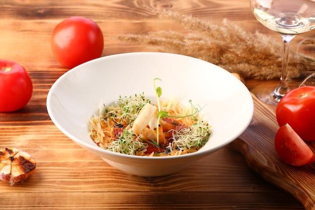 Zupa pomidorowa z kalmarem i serem ozdobiona mikrozieloną na drewnianym stole i białym winem