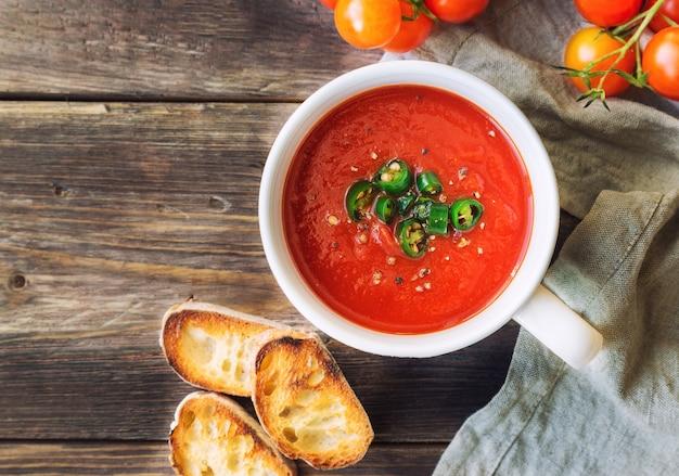 Zupa pomidorowa z papryką jalapeno i tostowym chlebem na rustykalne drewniane tła. widok z góry.