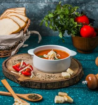 Zupa pomidorowa z parmezanem na kawałku drewna z pomidorami i krakersami dookoła.