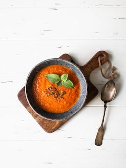 Zupa pomidorowa z przyprawami i świeżą bazylią na białym tle drewnianych.