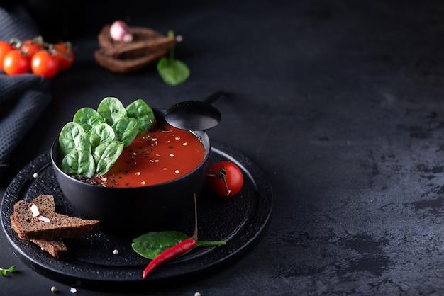 Zupa przecier pomidorowy ze szpinakiem w czarnej misce, zbliżenie