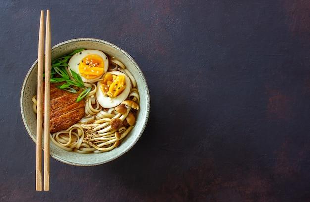 Zupa ramen z makaronem, wieprzowiną, grzybami i jajkami. kuchnia japońska. przepis.