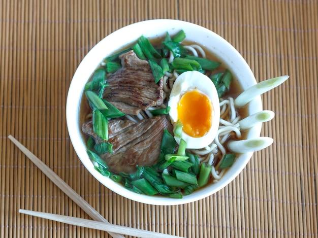 Zupa ramen ze świeżą cebulką, gotowanym jajkiem i smażonym mięsem