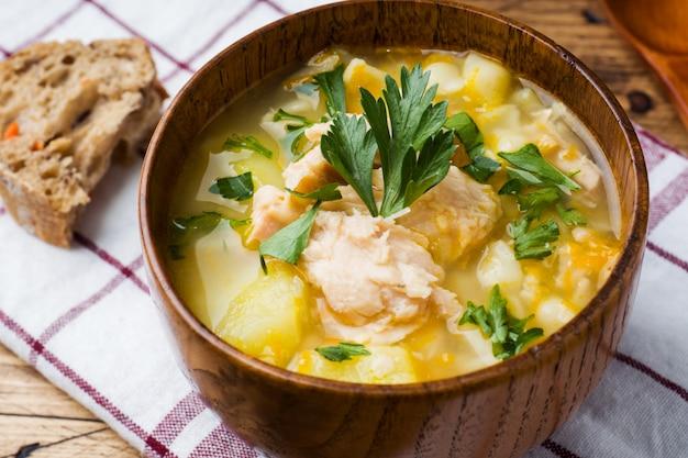 Zupa rybna w drewnianej misce ze świeżymi ziołami.