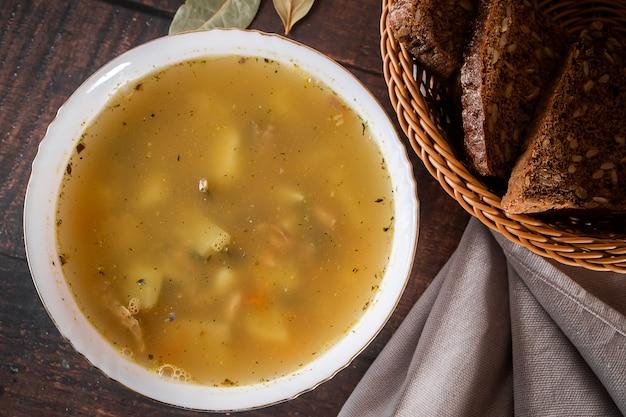 Zupa rybna w talerzu na brązowym tle. niskotłuszczowa zupa rybna w talerzu na brązowym tle