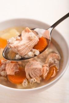 Zupa rybna z łososiem i perłą pomarańczową w łyżce