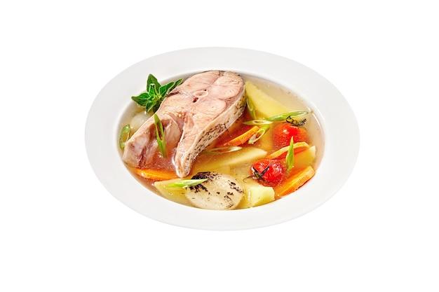 Zupa rybna ze stekiem z karpia srebrnego i warzywami na białym tle