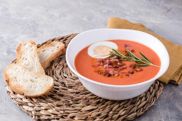 Zupa salmorejo, hiszpańskie tradycyjne danie. z szynką i jajkami w misce
