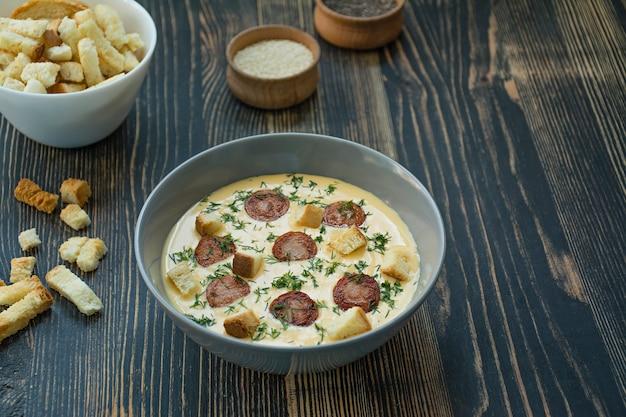 Zupa serowa z grillowanymi kiełbaskami i ziołami. zupa kremowa podawana na talerzu. ciemny drewniany stół.