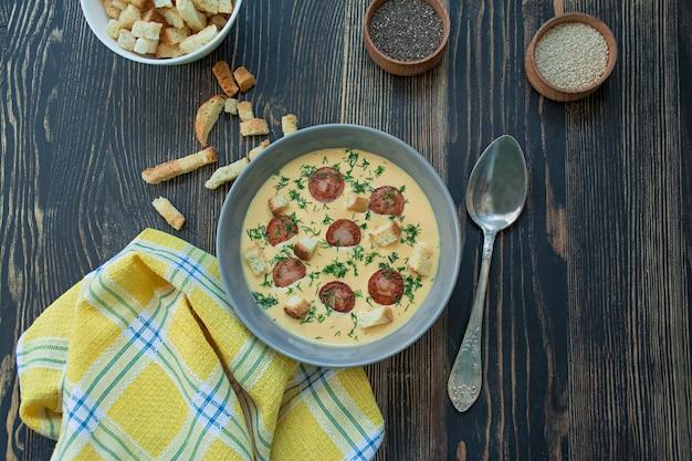 Zupa serowa z grillowanymi kiełbaskami i ziołami. zupa kremowa podawana na talerzu.