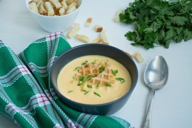 Zupa serowa z krakersami, ziołami i serem feta. zupa kremowa podawana na białym talerzu. biały