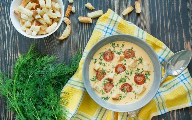 Zupa serowa ze smażonymi kiełbasami i ziołami. smaczna zupa serowa w białym talerzu. stół do jadalni. bilans zdrowego odżywiania. skopiuj miejsce drewniane tła.