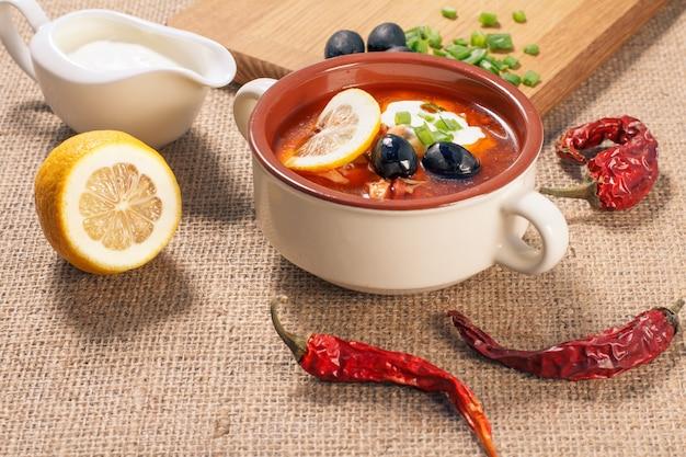 Zupa solankowa i kwaśna w ceramicznej misce do zupy, deska do krojenia z dodatkami, pokrojona cytryna i strąki gorzkiego pieprzu na worze.